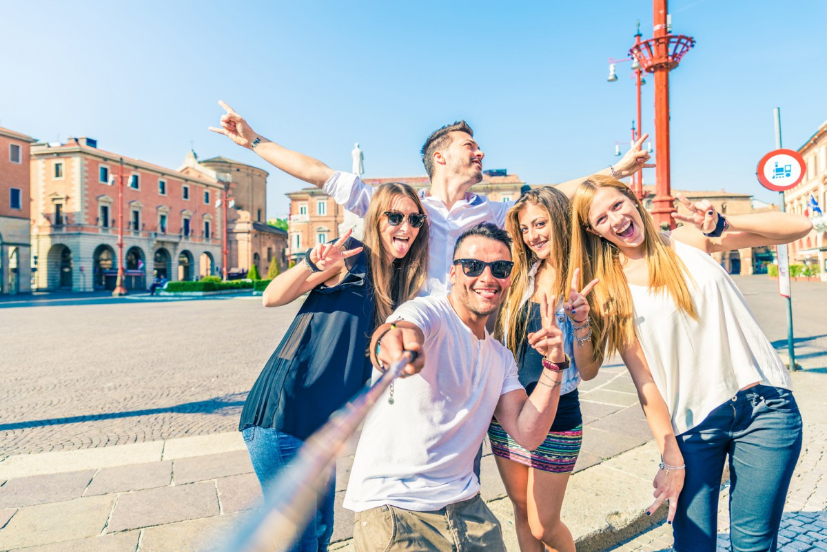 Group of happy friends taking a selfie with stick outdoors - Concept of young people having fun and using new communication tecnologies